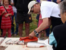 Salmon prep competition at Skidegate Days - a steady hand and a very sharp knife required ~ Photo Credit: R.Watkiss